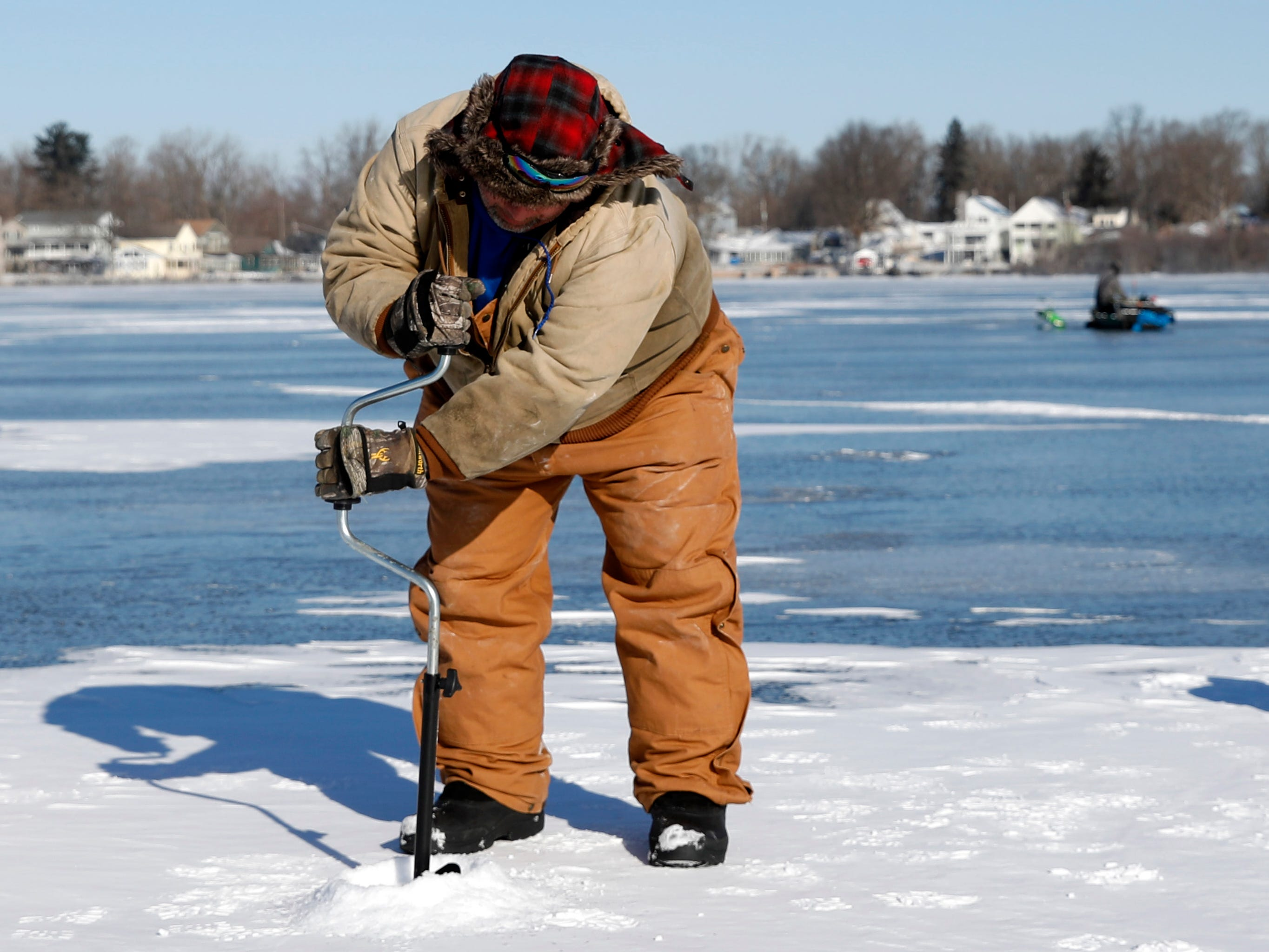 Keith Dilbeck uses an auger to drill a hole into the ice covered surface of Buckeye Lake Thursday morning, Jan. 31, 2019. Freezing temperatures this week have formed more than five inches of ice on the lake's surface, and despite single digit temperatures and a wind chill advisory several people took the opportunity to ice fish.