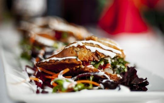 The empanadas at Israel's Delicias De Mexico Gourmet are filled with beef, cilantro and pico de gallo and garnished with sour cream on a bed of mixed greens. Jan. 31, 2019