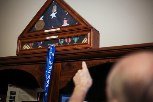 Charles Adams, a World War II veteran, shows off a shadow box filled with his medals, including his Purple Heart in his home in Bowling Green on Jan. 22, 2019.