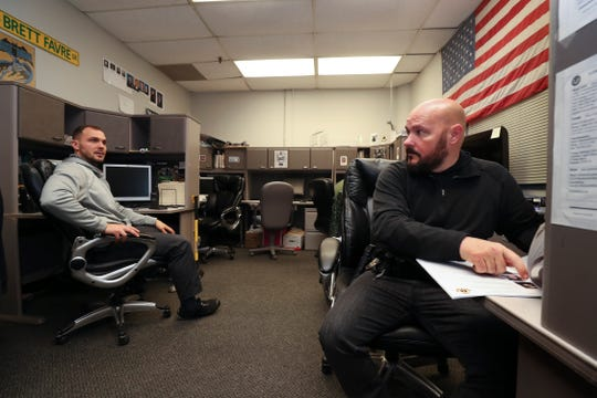 Fugitive Unit detectives Mike Woodard, right, and Tyler Holland discuss which suspects to surveil.  The unit is part of the 9th Mobile Division of the LMPD.Jan. 23, 2019