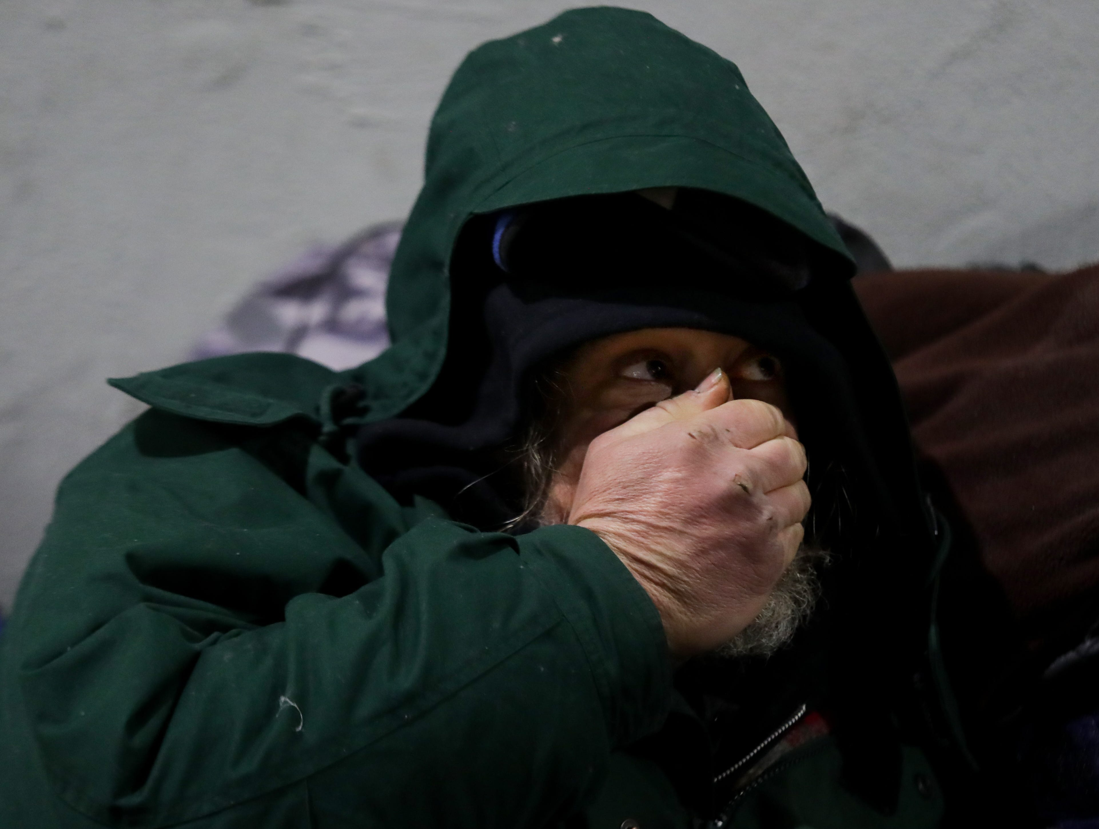 """Brian, a homeless man that goes by """"Detroit,"""" warms his hand under the viaduct on Jefferson between Preston and Jackson. Jan. 31, 2019"""