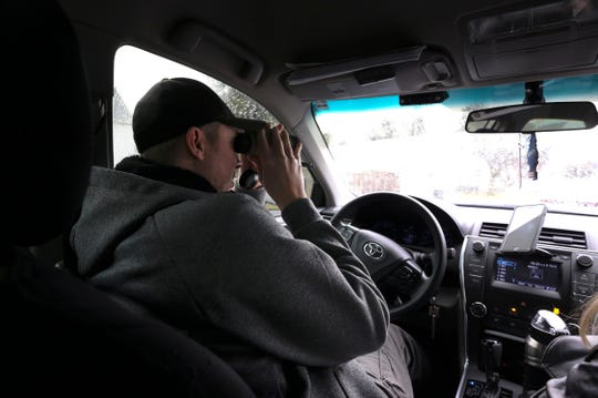 Sgt. Chris McMichael used binoculars to watch a residence during a recent stakeout.  He commands the Fugitive Unit inside the 9th Mobile Division of the LMPD.