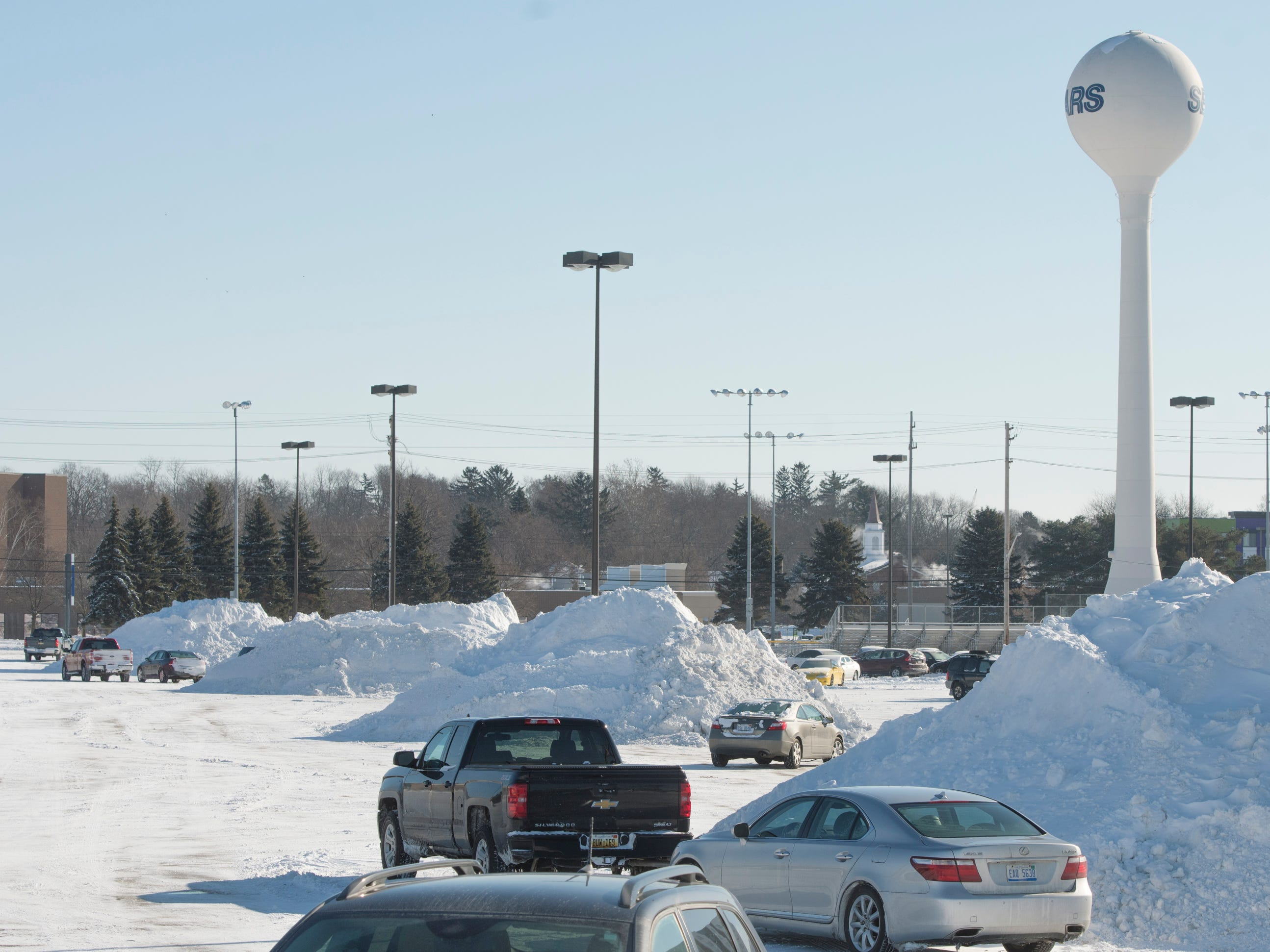 Mounds of snow are piled high throughout Frandor Shopping Center's parking lot Thursday, Jan. 31, 2019. Officials say river levels are expected to rise with warmer temperatures and snowmelt this weekend.