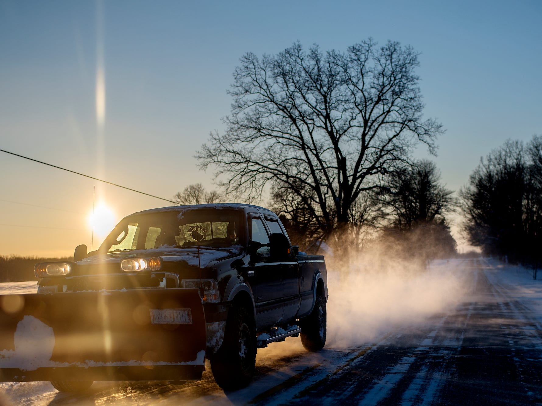 A plow truck travels along an icy Round Lake Road on Wednesday, Jan. 29, 2019, in Laingsburg.