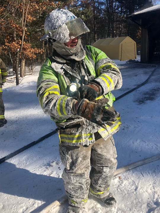 A firefighter is covered in ice while at the scene of a fire Wednesday in the Barron County village of Cameron.