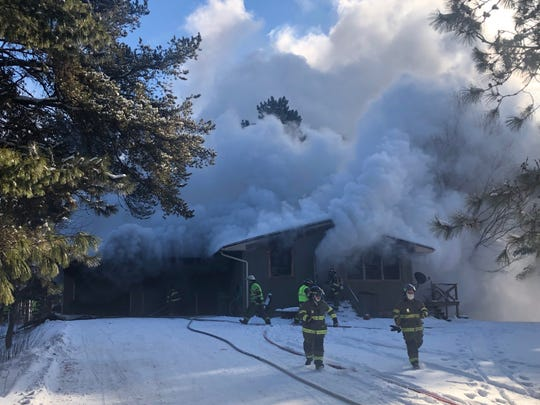 Firefighters at the scene of a house fire in the Barron County village of Cameron Wednesday.