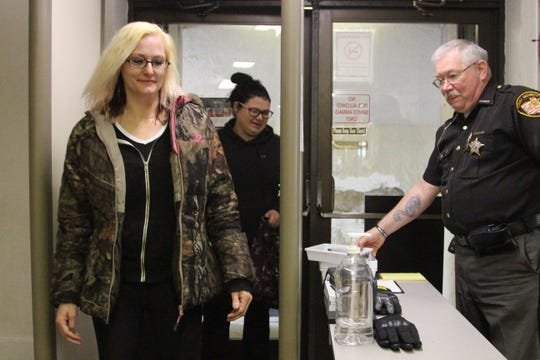 Andrea Thacker walks through a metal detector Tuesday at the entrance to the Marion County Courthouse. The courthouse did not have a metal detector regularly screening visitors to the courthouse until it was set up in mid-January.
