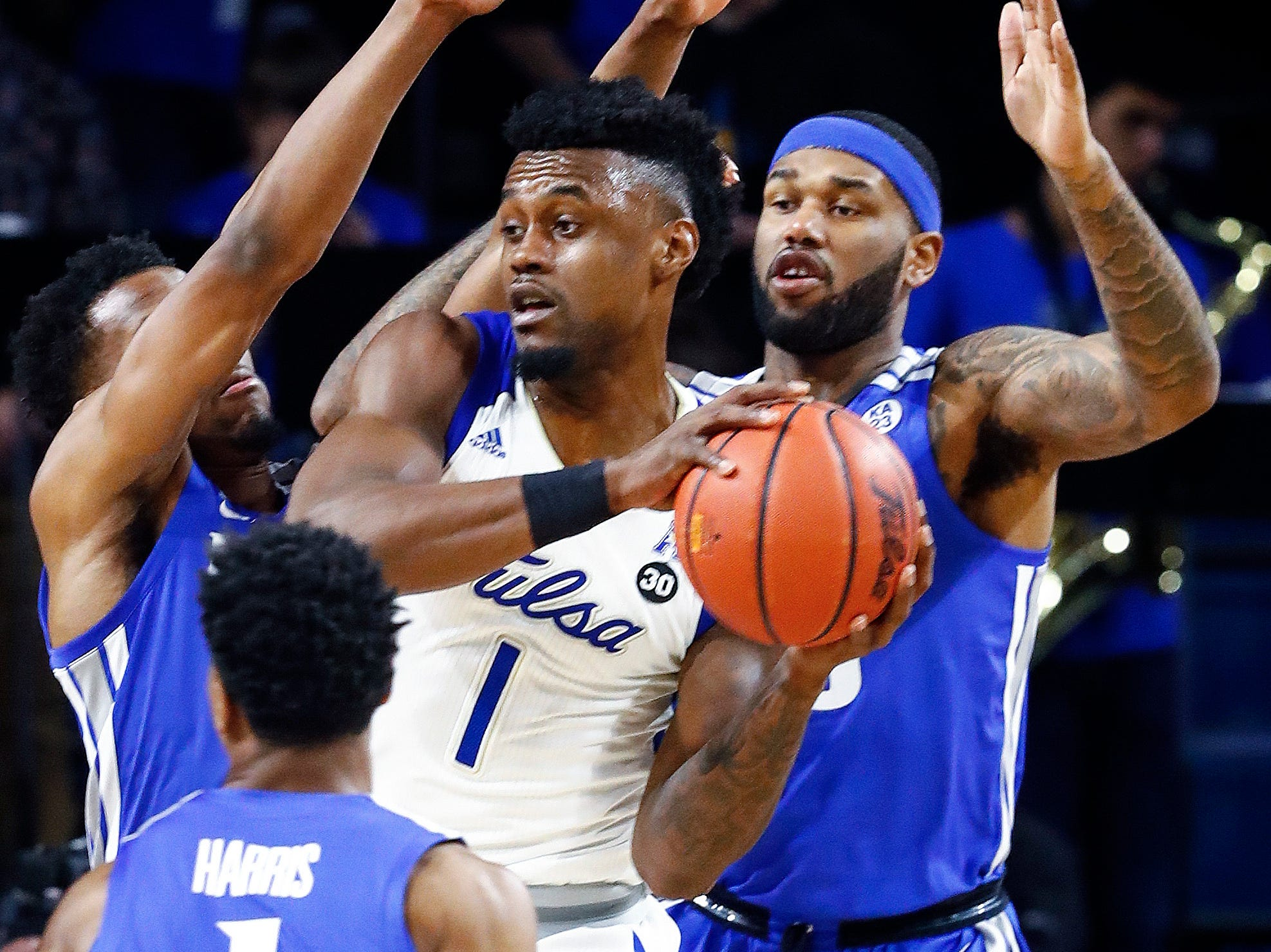 Memphis defenders Jeremiah Martin (left) and Mike Parks Jr. (right) apply defensive pressure to Tulsa forward Martins Igbanu (middle) during action in Tulsa, Wednesday, January 30, 2019.