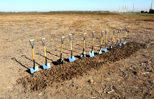Ground is broken on the new Electrolux facility in the Frank Pidgeon Industrial Park on Oct. 5, 2011. A total of 12 shovels stood ready to take part in the ceremony. The Allen Steam Plant is seen in distant background.