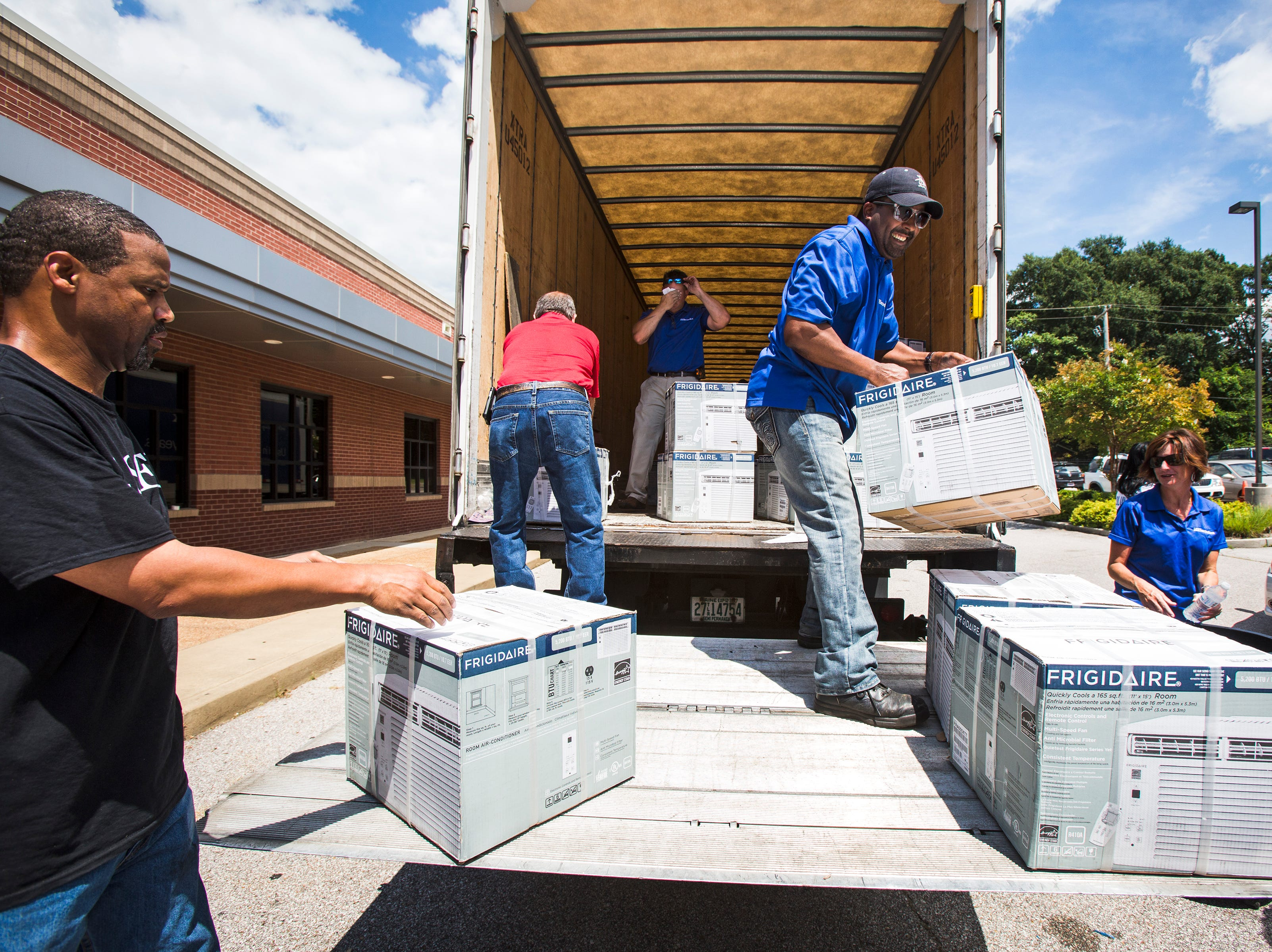 "July 16, 2014 - Zachary Kerr (left), a Neighborhood Christian Center employee, and Wilbur Oden (center), an Electrolux employee, unload boxes of air conditioners from a truck at NCC Wednesday afternoon. Electrolux donated 600 air conditioning units to local residents affected by high summer temperatures through its ""Keeping Memphis Cool"" initiative. Last July, the company donated 200 units valued at nearly $30,000. Priority was given to households with seniors 60 and older, disabled residents, and those on medical leave or who have been laid off from work."
