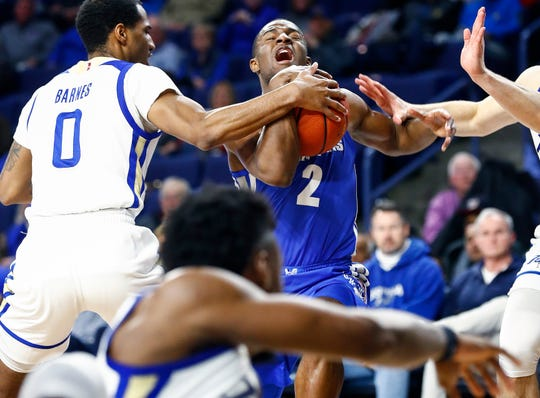 Memphis guard Alex Lomax is fouled while driving the lane against Tulsa defender Chris Barnes (right) during action in Tulsa,  Wednesday, January 30, 2019.