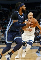 Memphis Grizzlies' Mike Conley, left, drives as Minnesota Timberwolves' Jerryd Bayless pursues in overtime of an NBA basketball game Wednesday, Jan. 30, 2019, in Minneapolis. The Timberwolves won 99-97.