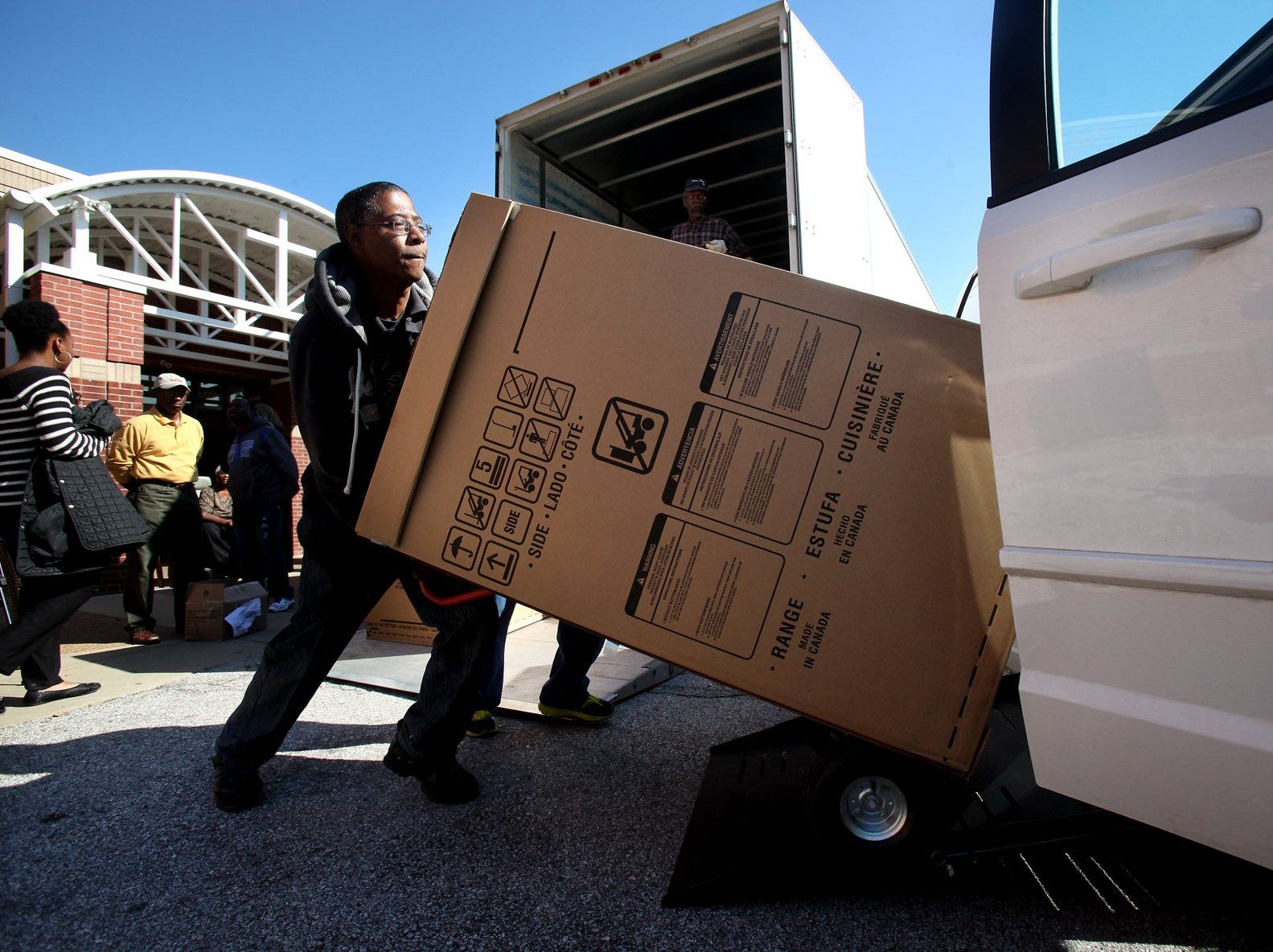 October 24, 2013 - (left) Ontario Simpson loads a free Electrolux oven into his van as the company gives away $100,000 worth of ovens and microwaves to community residents. (Kyle Kurlick/Special to The Commercial Appeal)