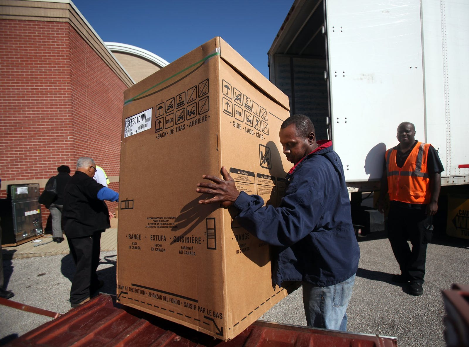October 24, 2013 - (center) Michael Stamps loads a free Electrolux oven into his truck as the company gives away $100,000 worth of ovens and microwaves to community residents. (Kyle Kurlick/Special to The Commercial Appeal)