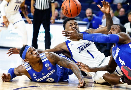 Memphis defenders Kyvon Davenport (left) and Raynere Thornton (right) lose a loose battle to Tulsa guard Martins Igbanu (middle) during action in Tulsa,  Wednesday, January 30, 2019.