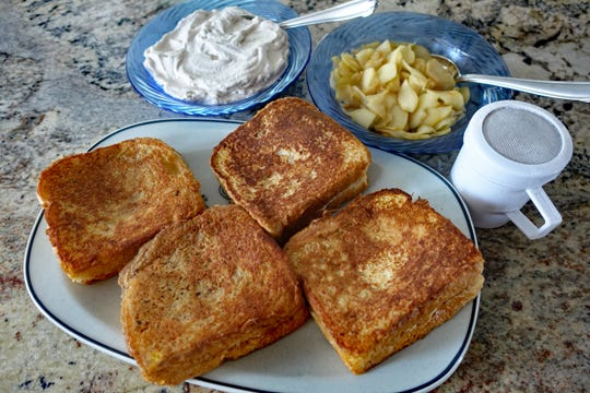 Stuffed French Toast is served with cinnamon whipped cream, sauteed apples and powdered sugar for dusting.