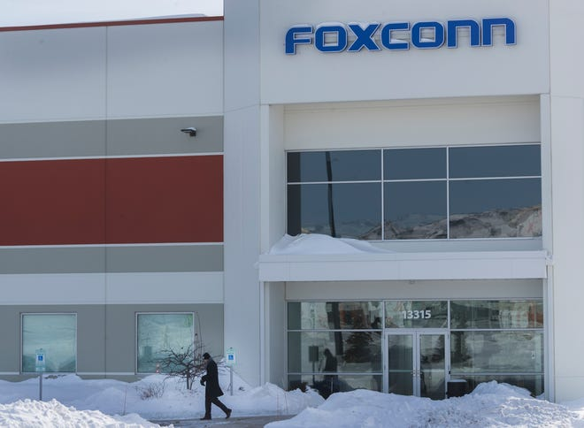 """A man exits the Foxconn building on Globe Drive Thursday in Globe Drive in Mount Pleasant. A Japan-based news outlet is reporting Taiwanese tech giant Foxconn is suspending work on its planned $10 billion plant in southeastern Wisconsin and a second plant in China, but the company says its plans are """"unchanged."""""""
