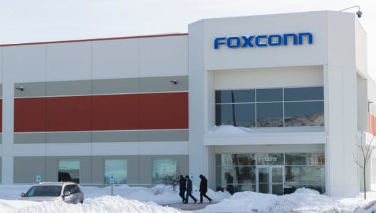 "A group exits a Foxconn building Thursday, January 31, 2019 in Globe Drive in Mount Pleasant,Wis. A Japan-based news outlet is reporting Taiwanese tech giant Foxconn is suspending work on its planned $10 billion plant in southeastern Wisconsin and a second plant in China, but the company says its plans are ""unchanged."""