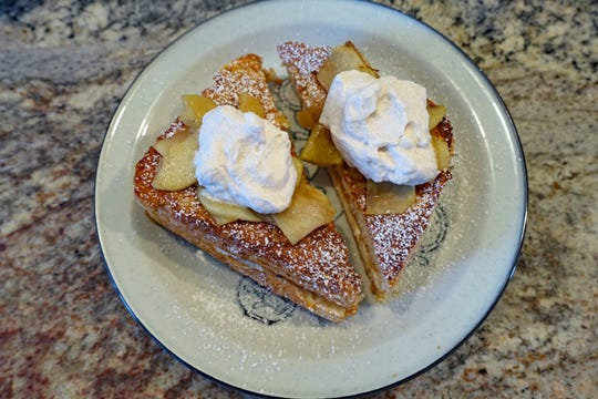 French toast stuffed with cream cheese and apple jam and topped with apples and whipped cream is a rich, sweet way to start the day.