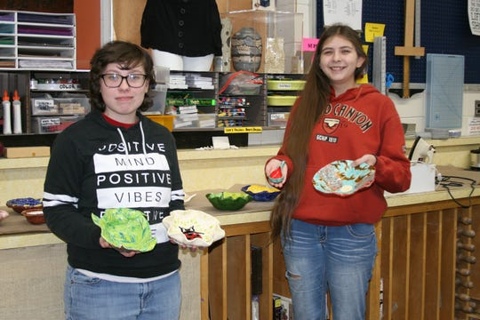 Mountain Home High School Art Club member Chloe Leahy (left) and president Breanna Hickmont, both seniors, display some of the 125 artist-created bowls that will be given to the first 125 patrons of the annual Empty Bowls to Feed the Hungry soup dinner to benefit the Food Bank of North Central Arkansas on Thursday, Feb. 7.