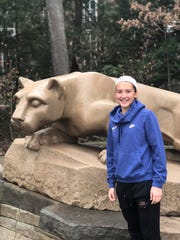 Delta soccer star Addie Chester poses with the nittany lion statue on the campus of Penn State University.