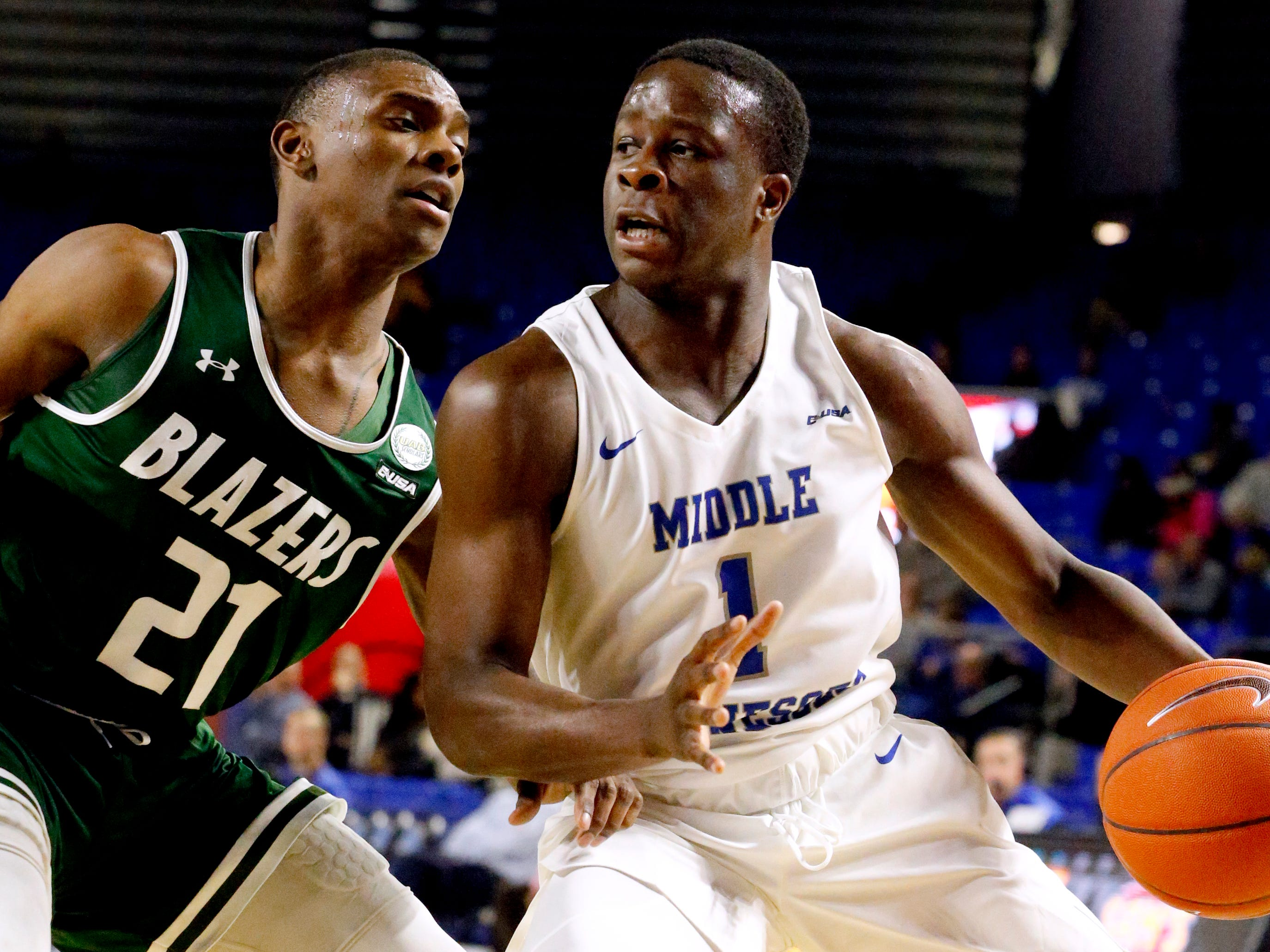 MTSU guard Junior Farquhar (1) drives to the basket as UAB's guard Jalen Perry (21) guards him on Wednesday Jan. 30, 2019.