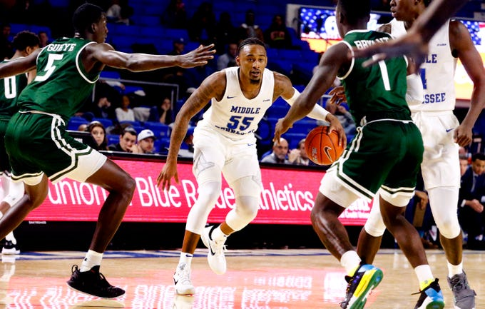 MTSU guard Antonio Green (55) looks of a path to the basket between UAB's forward Makhtar Gueye (5) and UAB's guard Zack Bryant (1) on Wednesday, Jan. 30, 2019.