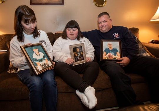 (From left) Jessica, Katie and Bobby Lawrence hold pictures of B.J. Lawrence, who died last summer of an undetected heart issue.