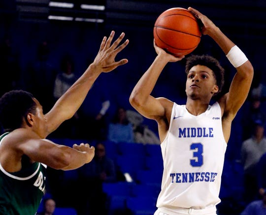 MTSU guard Donovan Sims (3) shoots a three point basket as UAB's guard Jeremiah Bell (2) guards him on Wednesday Jan. 30, 2019.
