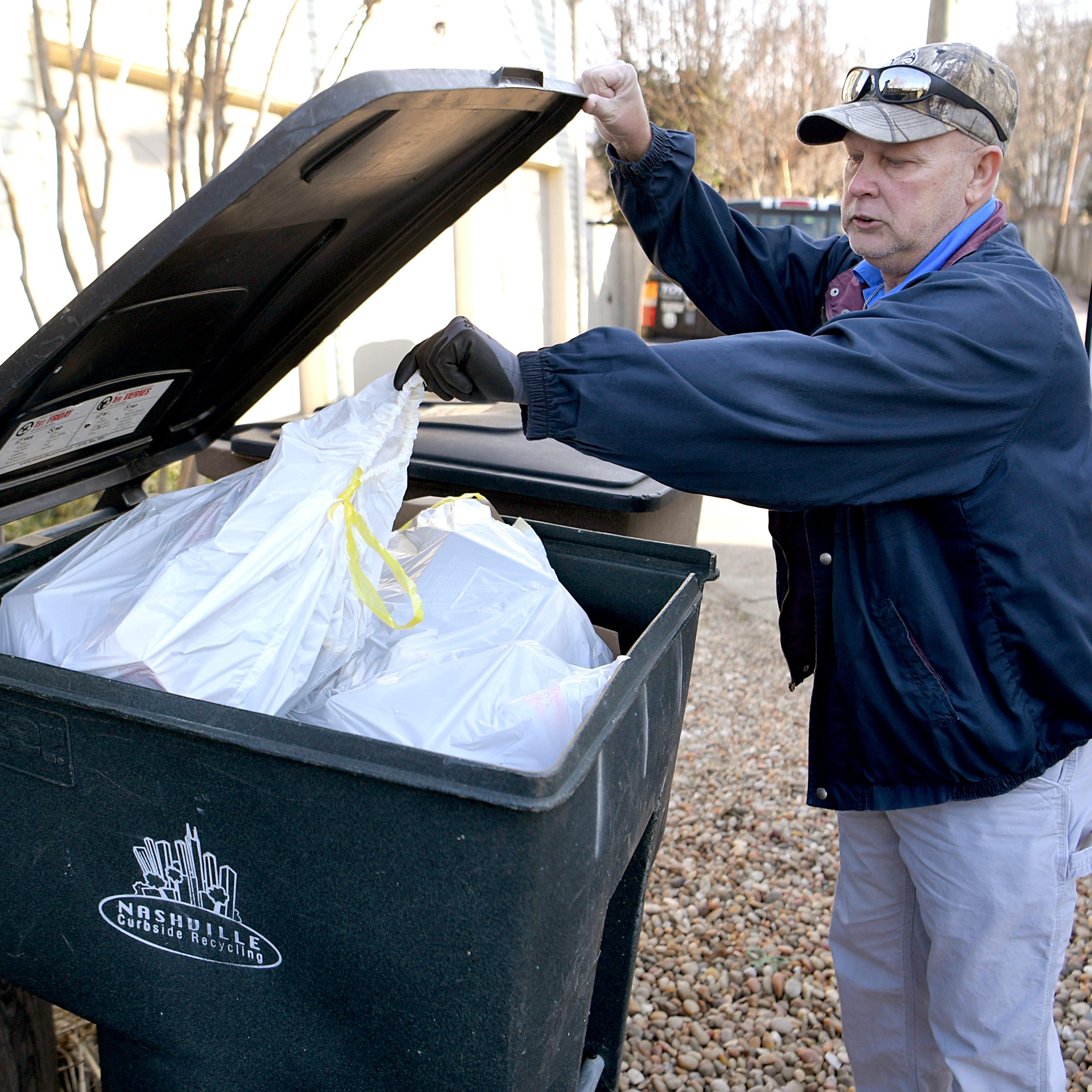 Public Works employee Ricky Lloyd inspects a...