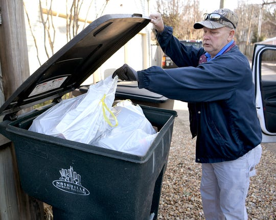 Public Works employee Ricky Lloyd inspects a resident's recycling can to look for non-recyclable items. He will place a sticker on the can to notify residents of items not allowed in the recycling stream.