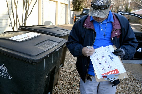 Public Works employee Ricky Lloyd inspects a resident's recycling can to look for non-recyclable items.  He will place a sticker notifying residents of items not allowed in the recycling stream.