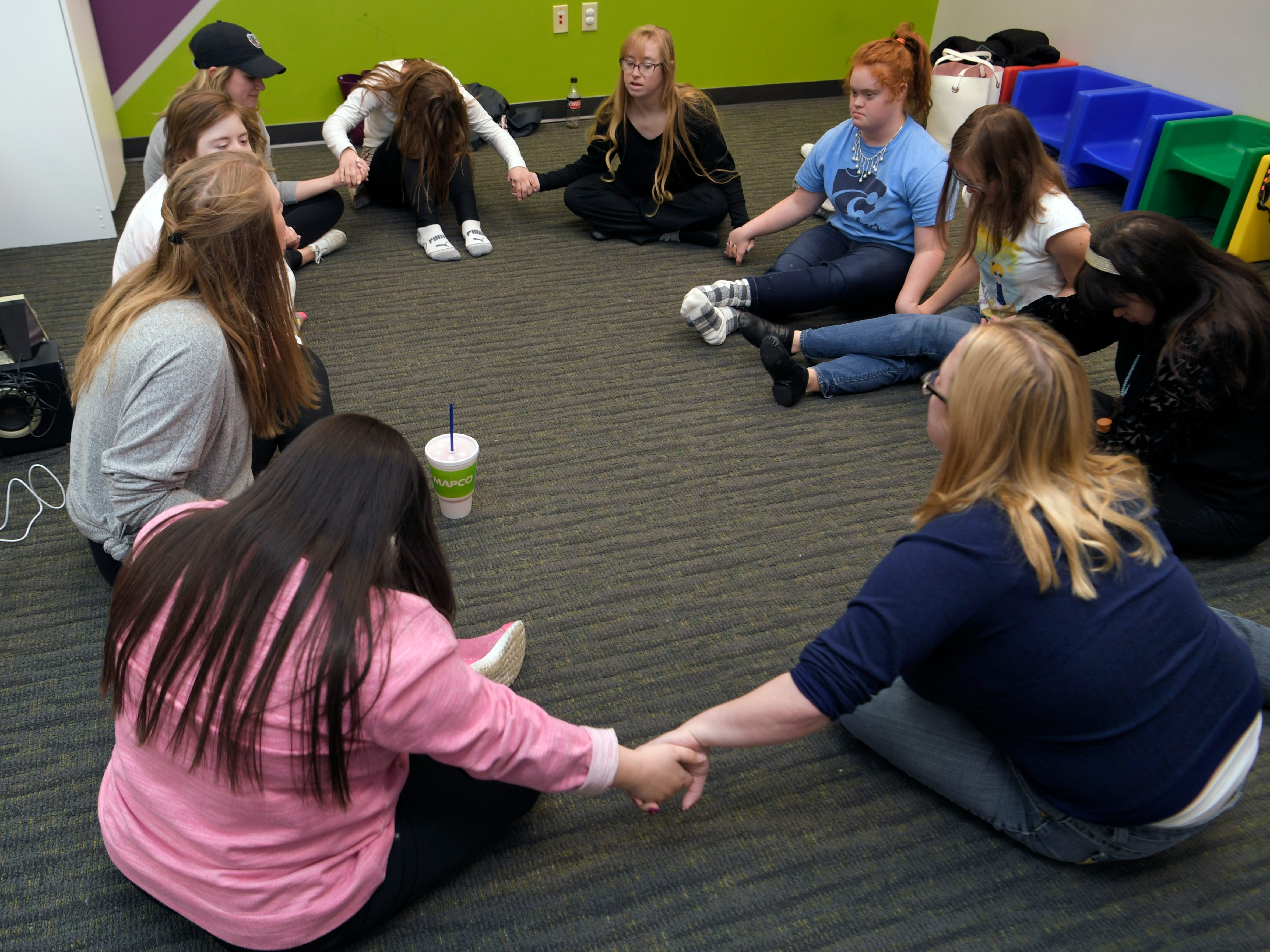 Dancing Divas team members hold hands in pray before practice at GiGi's Playhouse in Brentwood on Saturday, Jan. 5, 2019.  Dancing Divas is a special needs dance team created to help dance members to grow physically, mentally, and emotionally while proving ability and value.