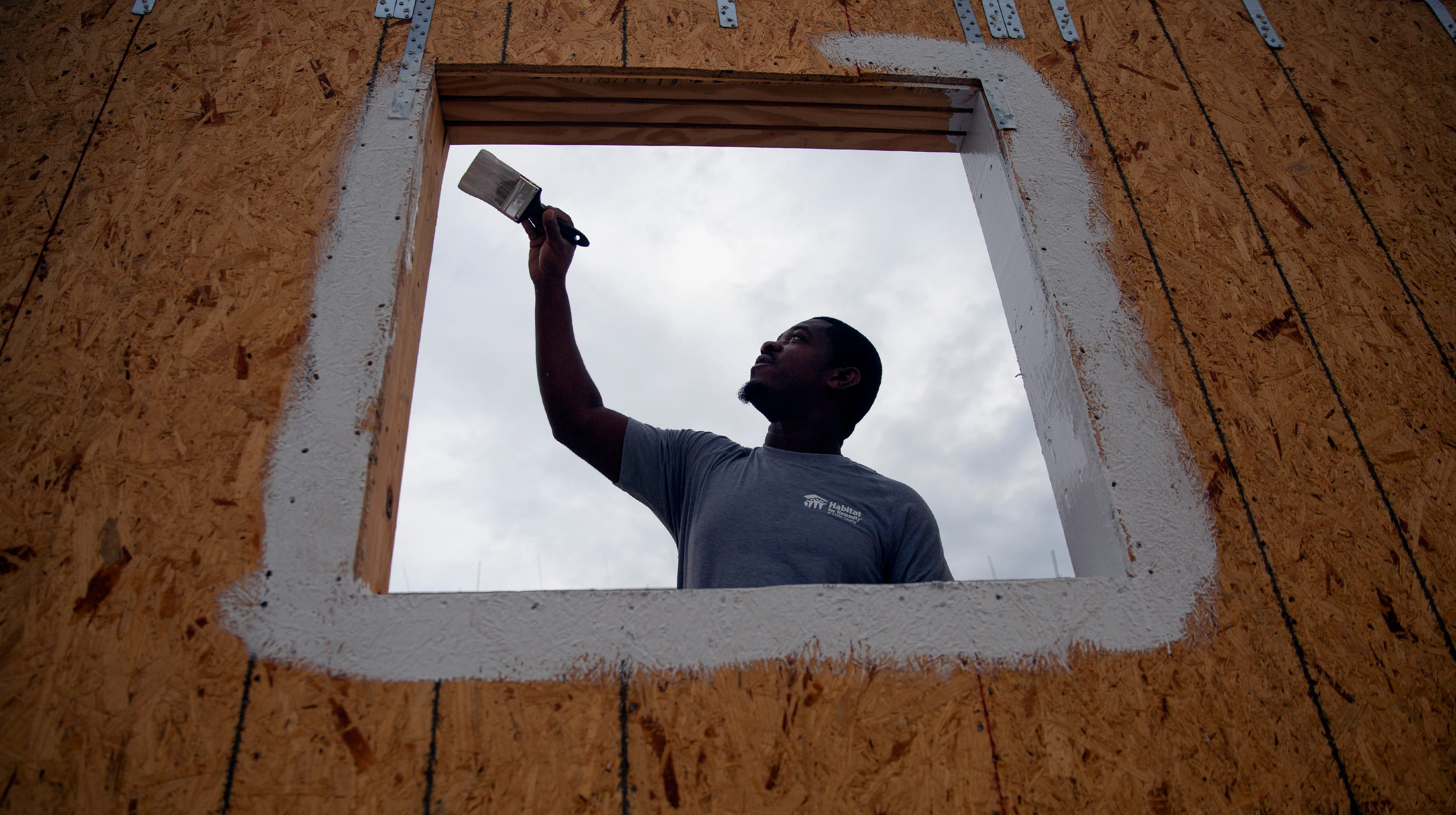 Billy With, a site supervisor for Habitat for Humanity of Collier County, applies a protective coating on a window,  Saturday, Jan. 5, 2019, in the Dockside neighborhood southeast of Naples.