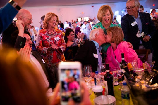 Rodney and Kathy Woods kiss after winning lot 23, a 10 night trip through Italy, during the Naples Winter Wine Festival at the Ritz-Carlton Golf Resort in Naples on Saturday, January 26, 2019.