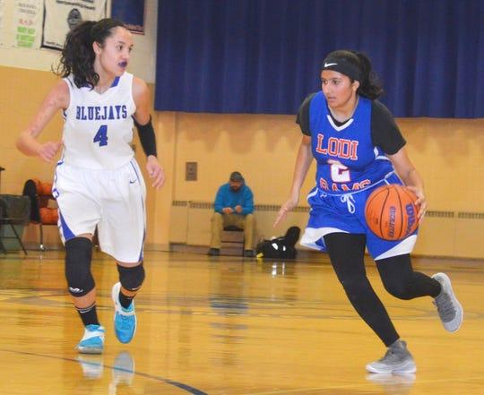 Lodi sophomore guard Kashmala Arif dribbles the basketball as Mary Help junior guard Emily Toresi defends.