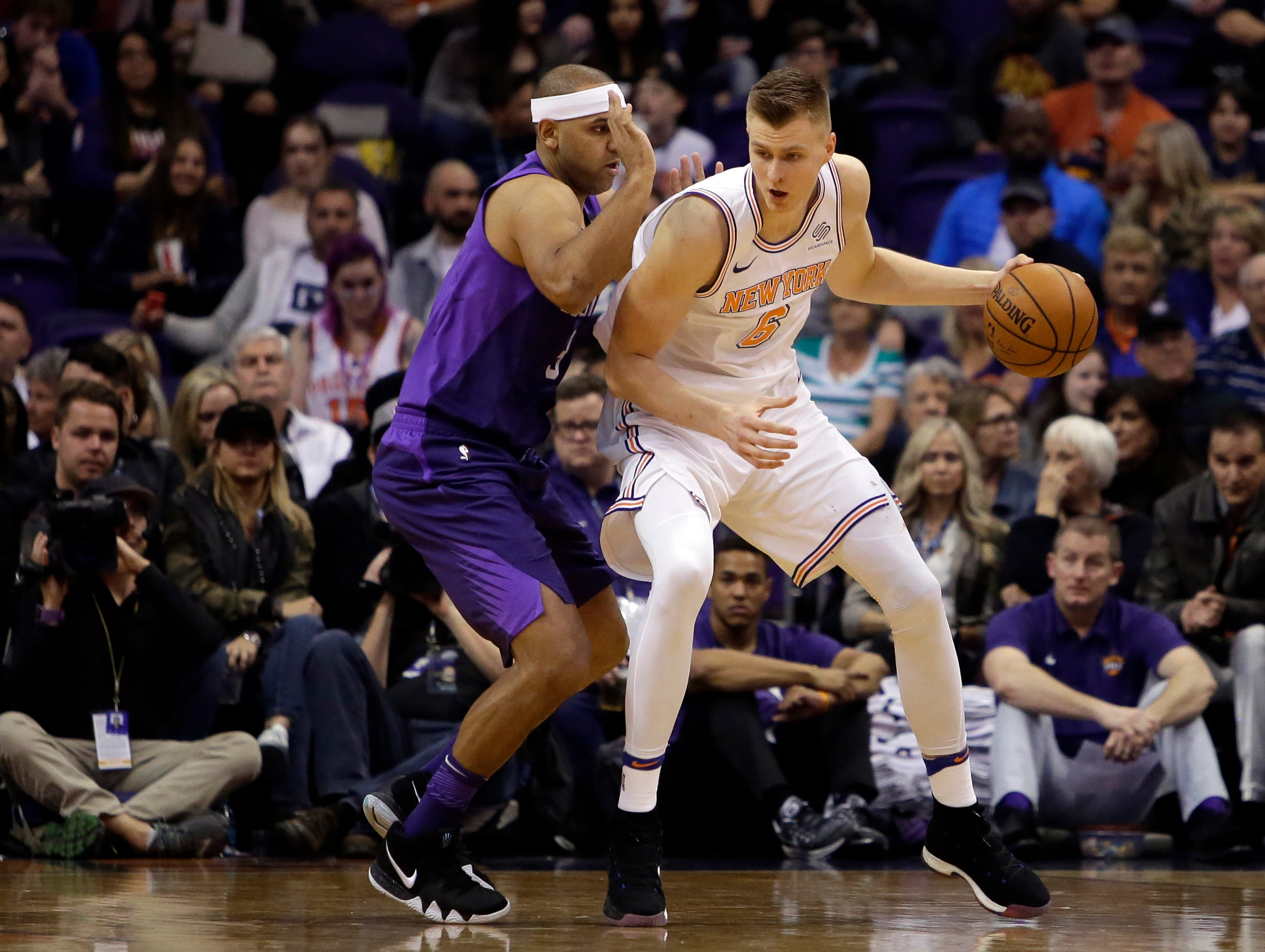 FILE - In this Jan. 26, 2018, file photo, New York Knicks forward Kristaps Porzingis (6) controls the ball in the first half of an NBA basketball game against the Phoenix Suns in Phoenix. Porzingis' left knee is healing well from a torn ACL and he will be re-evaluated in mid-February 2019. (AP Photo/Rick Scuteri, File)