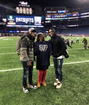 Patriots teammates and twins Jason and Devin McCourty pose with their mom, Phyllis Harrell, on the field at Gillette Stadium in Foxborough, Mass., after New England clinched the AFC East title.