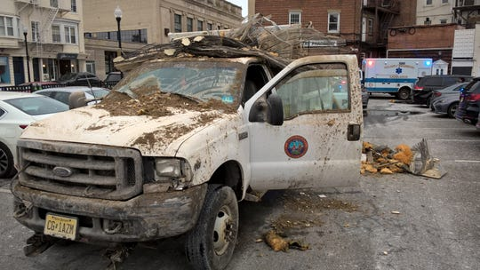 A Bergen County owned dump truck is filled with debris after a driver ripped a ceiling of a parking garage in Ridgewood.