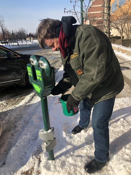 Don Campbell a parking meter technician for the City of Birmingham, collects coins from the meters to prevent jamming during Wednesday's frigid sub-zero temperatures.