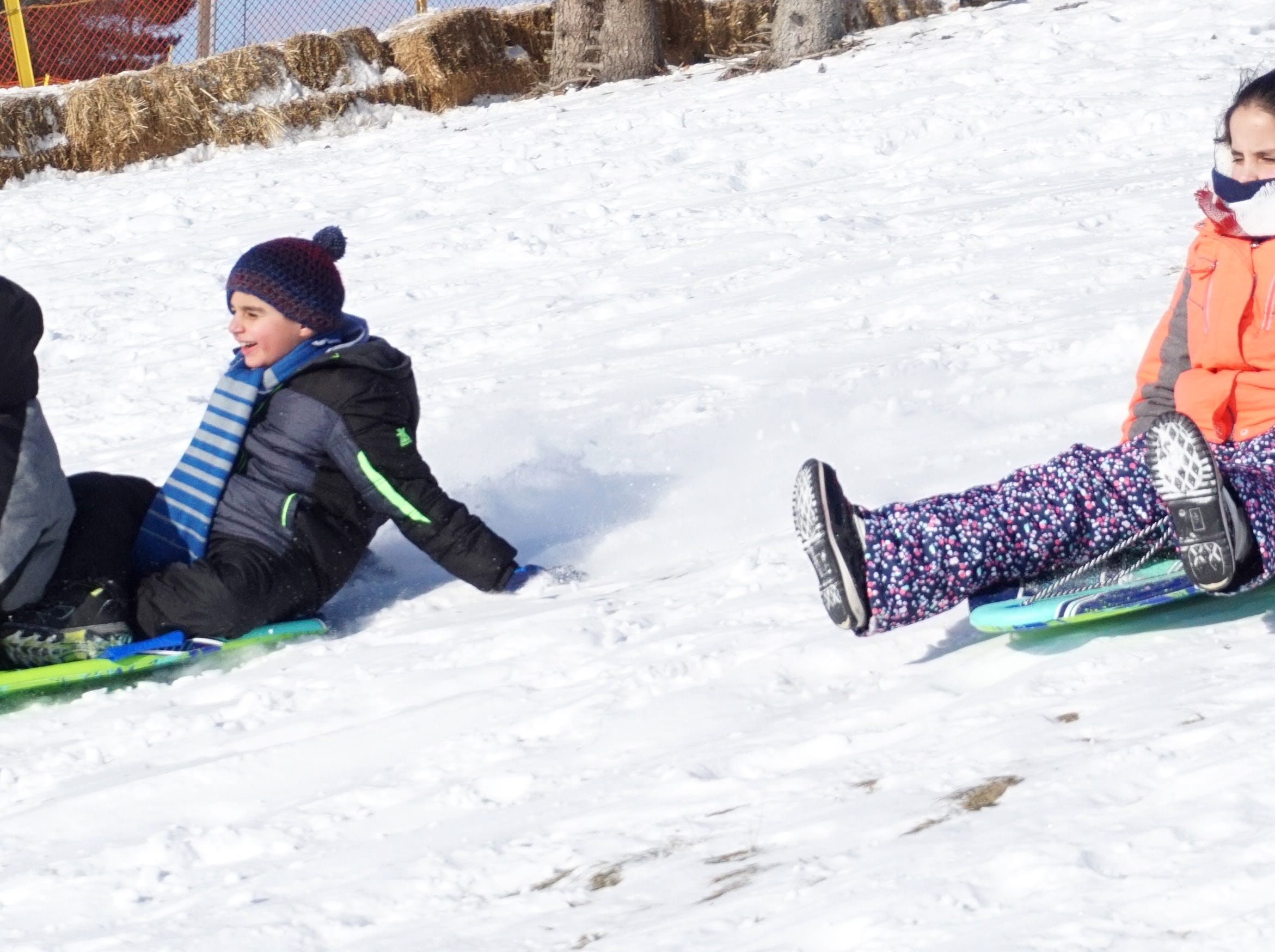 Siblings Thomas, 12, Mathhew, 9 and Theresa Keriko, 9, zip down the hill at the Farmington Public Schools building off Shiawasee on Jan. 31. The kids were there with their mother Dena - and the only ones at that time brave enough to take on the chill of that afternoon.