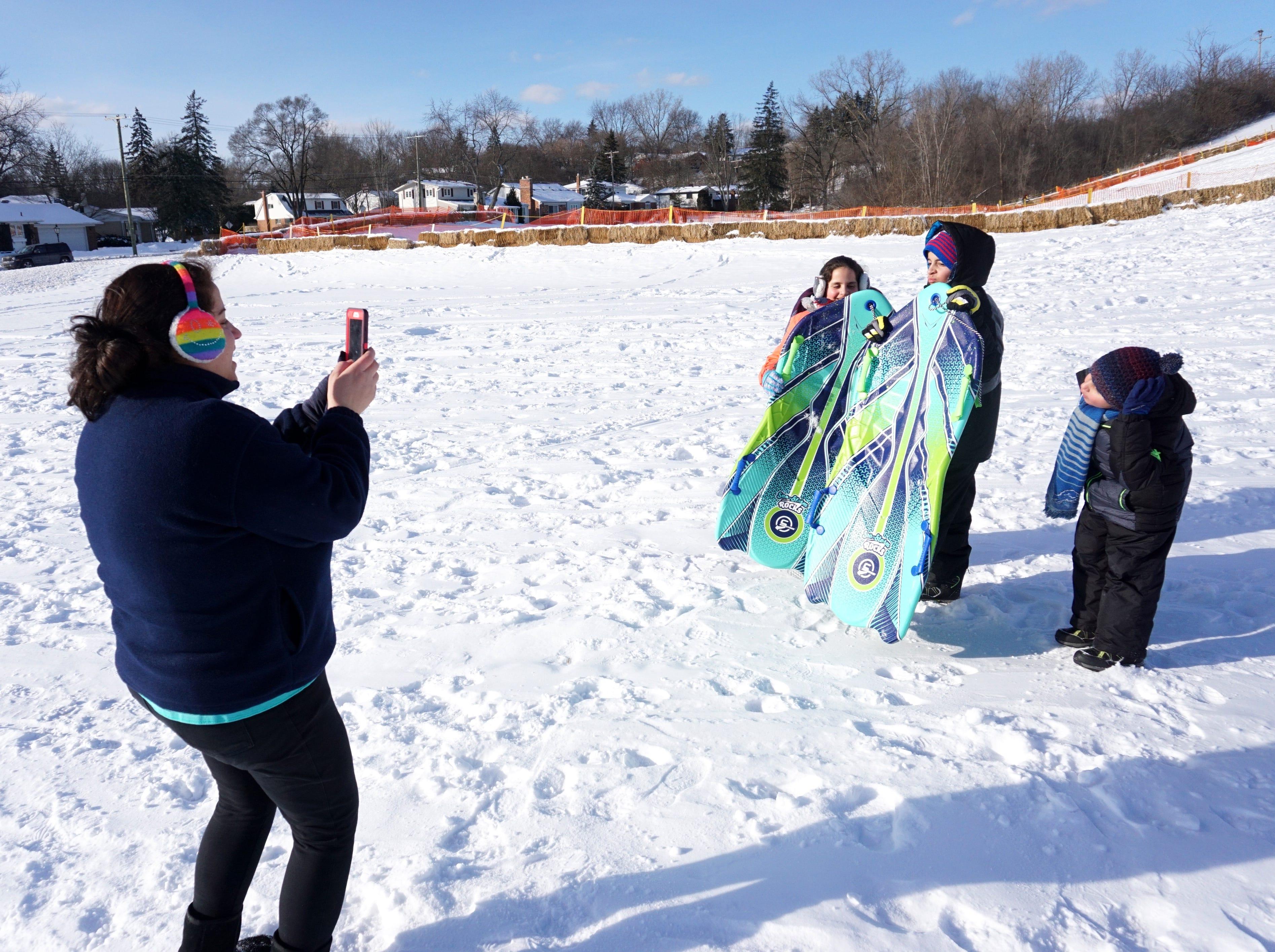 Dena Keriko gets a photo of her sledding kids Theresa, Thomas and Matthew on Thursday afternoon in Farmington.