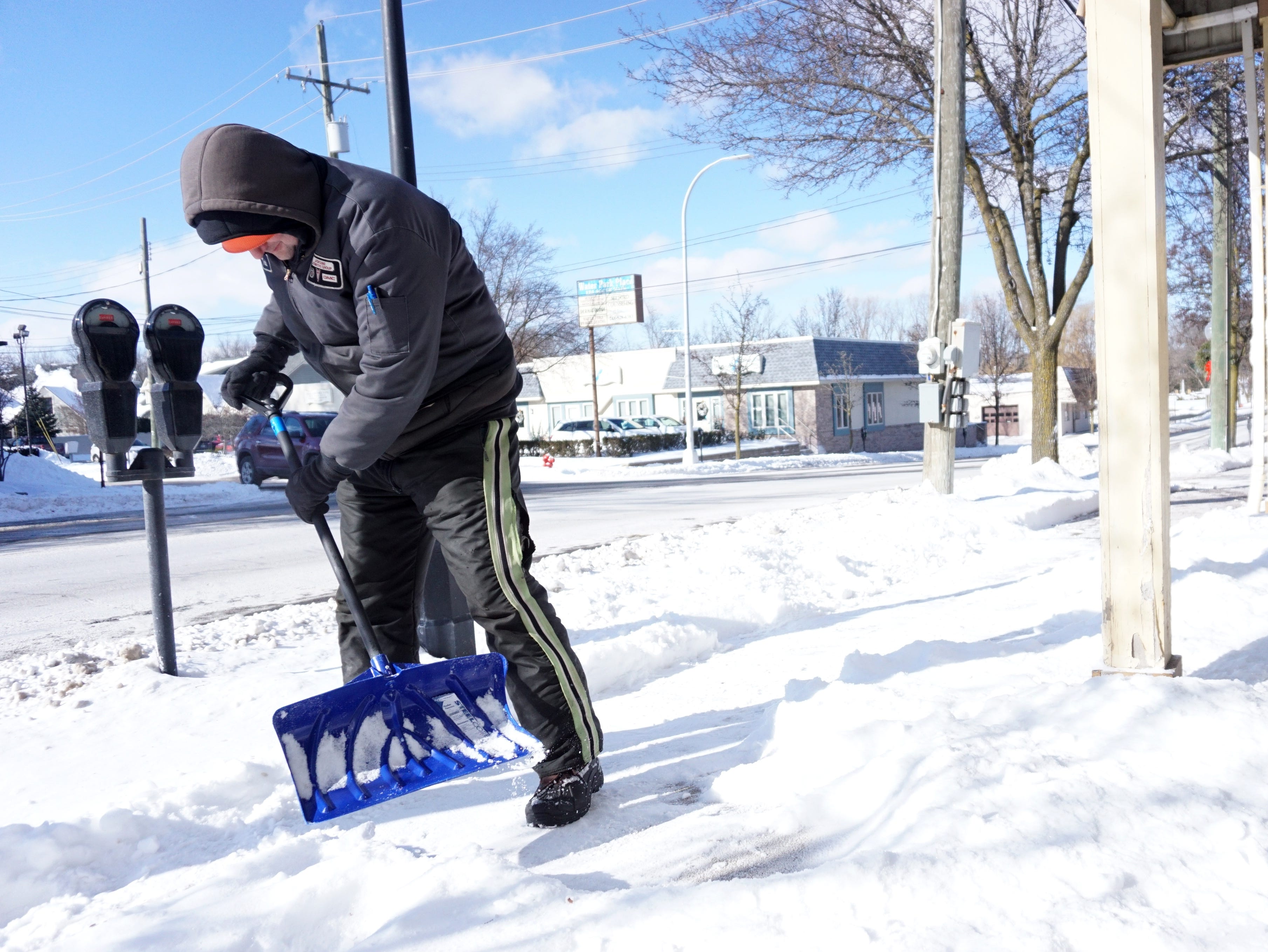 LaFontaine Auto employee Todd Cook digs away at some of the accumulated snow near the Milford dealership on Jan. 31. Even though it was warmer than Wednesday, it was still only about 4 degrees at the time of this photo.