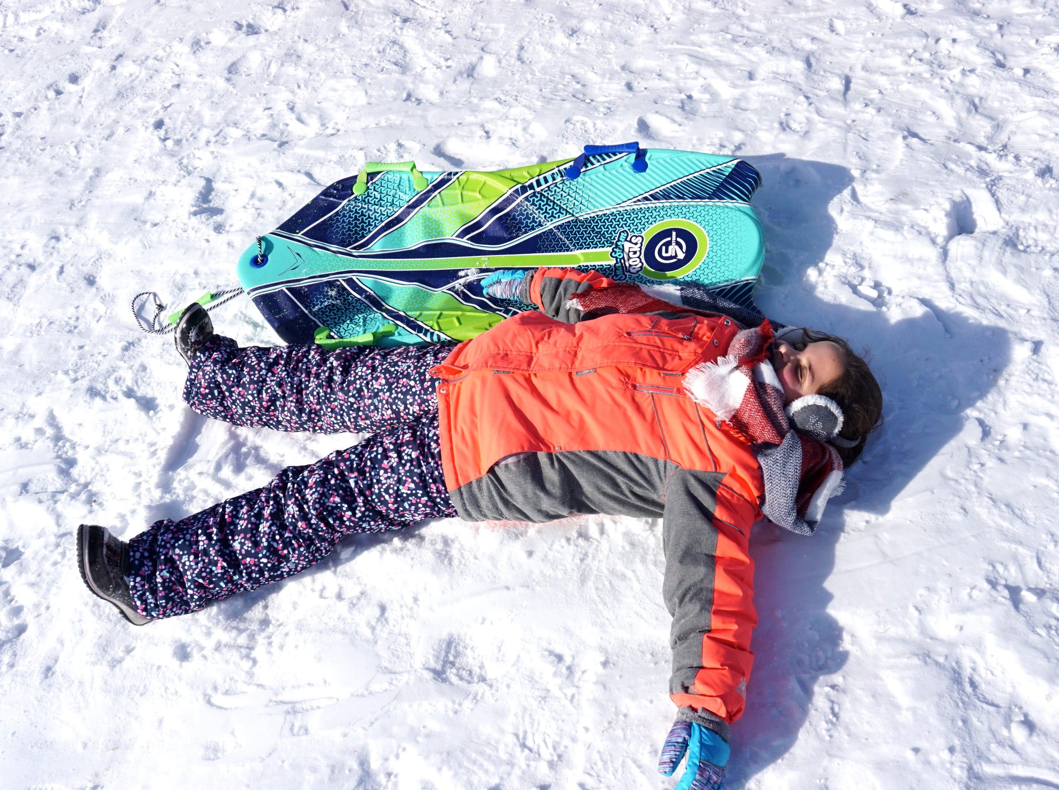 An exhausted Theresa Keriko, 9, takes a break from sledding in Farmington on Jan. 31.