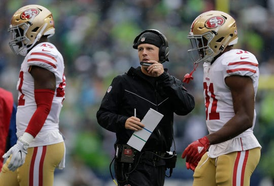 San Francisco 49ers wide receivers coach Mike LaFleur talks into his headset during a 2017 game against the Seattle Seahawks.