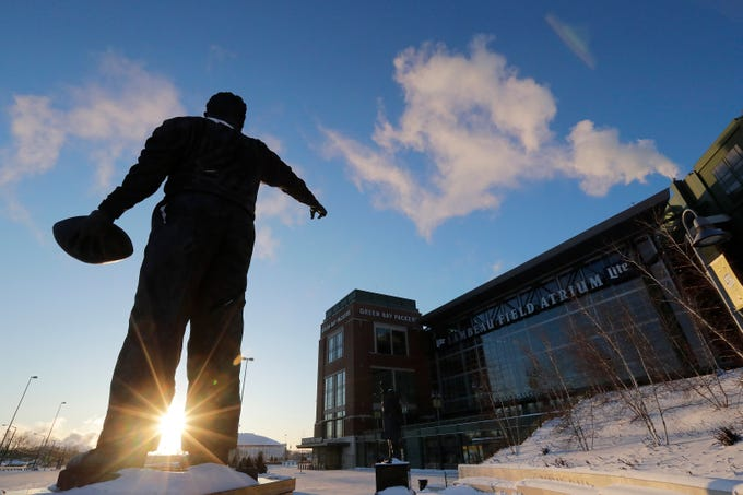 The rising sun is shown behind the Curly Lambeau statue with temperatures around -20 at Lambeau Field on Thursday, January 31, 2019 in Green Bay, Wis.