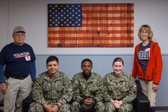 USO volunteers Chuck Woodland, far left, and Donna King, far right, pose with sailors attached to Information Warfare Training Command Corry Station at Naval Air Station Pensacola Corry Station on Jan. 25.