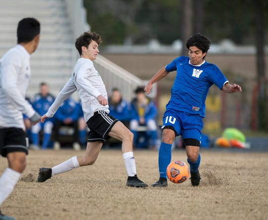 Jack Patching (17) tries to pass the ball past Christian Garcia (10) during the Navarre vs Washington soccer game at Booker T. Washington High School in Pensacola on Wednesday, January 30, 2019.  The Raiders defeated the Wildcats 5 -1.