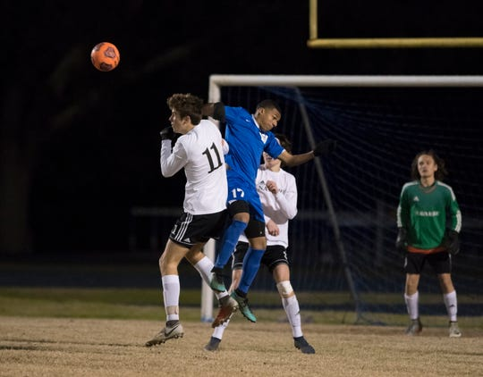 Mason Fralick (11) and Kendrick Hernandez (17) leap for the ball during the Navarre vs Washington soccer game at Booker T. Washington High School in Pensacola on Wednesday, January 30, 2019.  The Raiders defeated the Wildcats 5 -1.