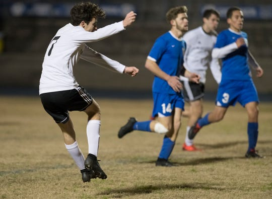 Jack Patching (17) watches as his kick goes in for a goal during the Navarre vs Washington soccer game at Booker T. Washington High School in Pensacola on Wednesday, January 30, 2019.  The Raiders defeated the Wildcats 5 -1.